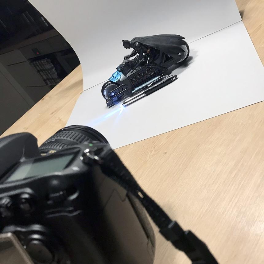 DSLR on mini tripod, grey card backdrop, LED torch pen and Batman Toy